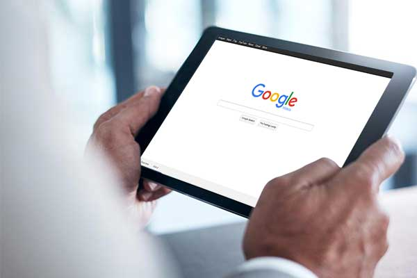 hands-holding-tablet-viewing-google-homepage